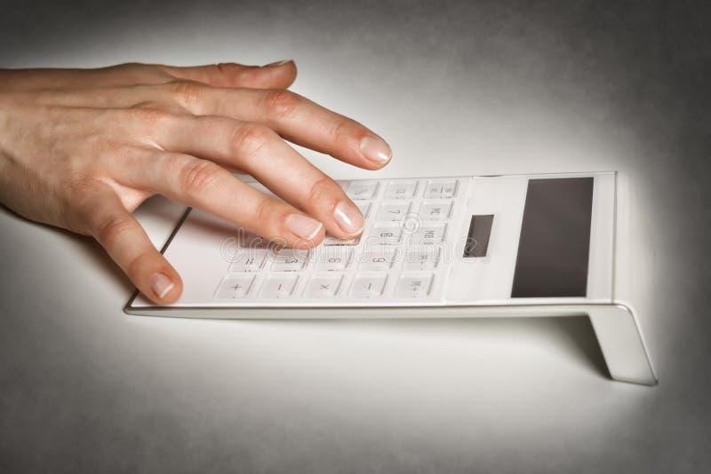 Mano femenina con la calculadora imagenes de archivo