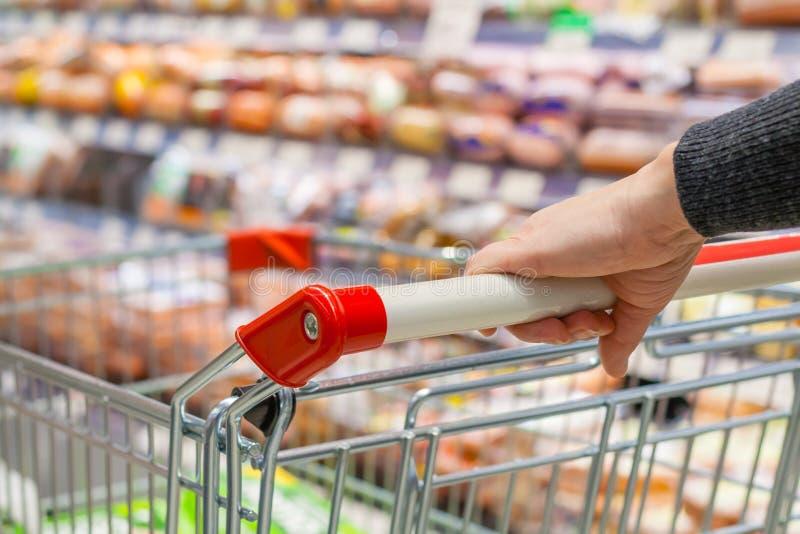 Mano femenina con la carretilla de mano en supermercado fotografía de archivo