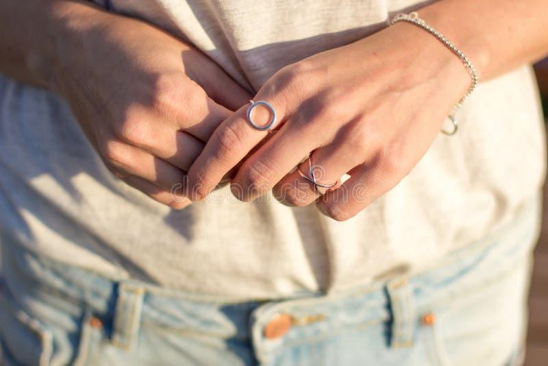 Mano femenina con la joyería, los anillos de plata y las pulseras minimalistas imagen de archivo