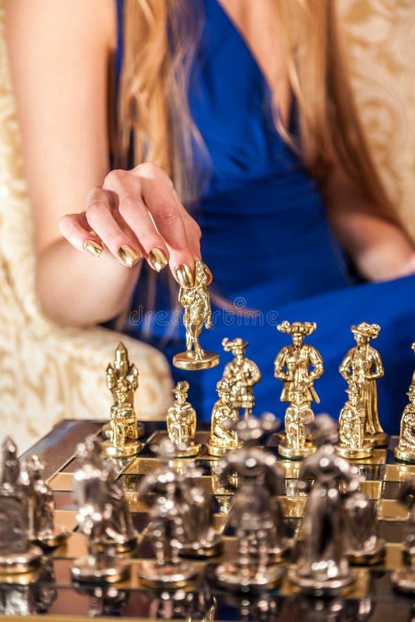 Mano femenina con la manicura elegante del oro que lleva a cabo el pedazo de ajedrez imagen de archivo libre de regalías