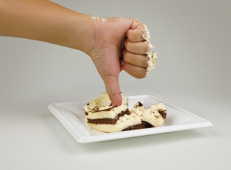 Mano femenina con un finger abajo Pulgares abajo en el fondo de la torta Torta no sabrosa Torta de la aversión El concepto es des imagen de archivo libre de regalías