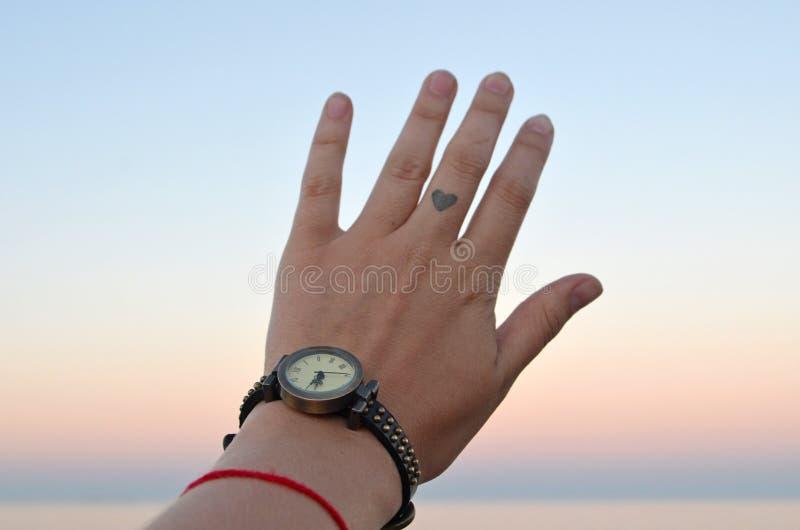 Mano femenina con un reloj foto de archivo