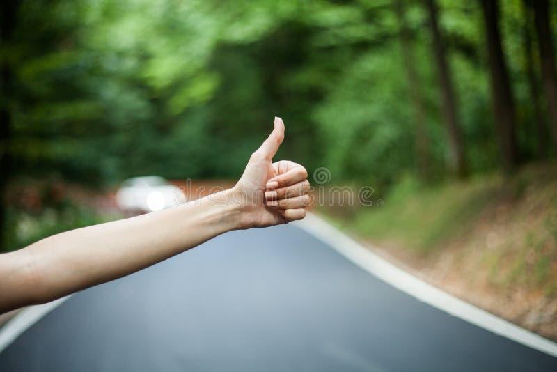 Mano femenina de los autostopistas que para el coche imágenes de archivo libres de regalías