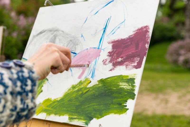 Mano femenina del artista que pinta un bosquejo de la imagen en el ai abierto imagen de archivo