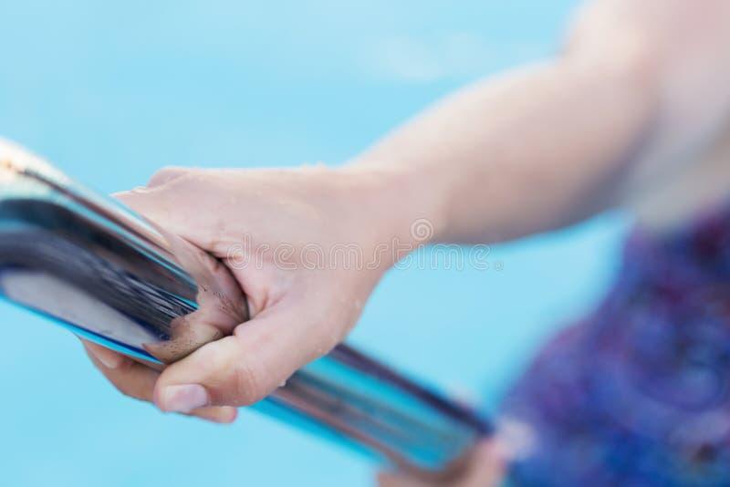 Mano femenina del ` s que sostiene una barandilla en una piscina foto de archivo