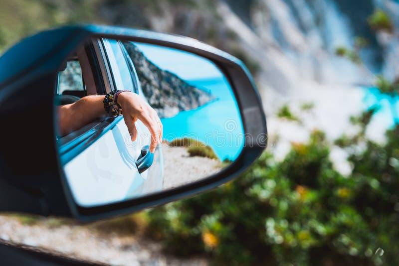 Mano femenina duplicada en el espejo de la vista lateral del coche Mar Mediterráneo azul y rocas blancas en fondo imagenes de archivo