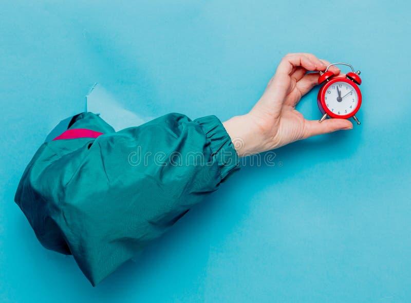 Mano femenina en despertador de la tenencia de la chaqueta del estilo 90s imagen de archivo libre de regalías