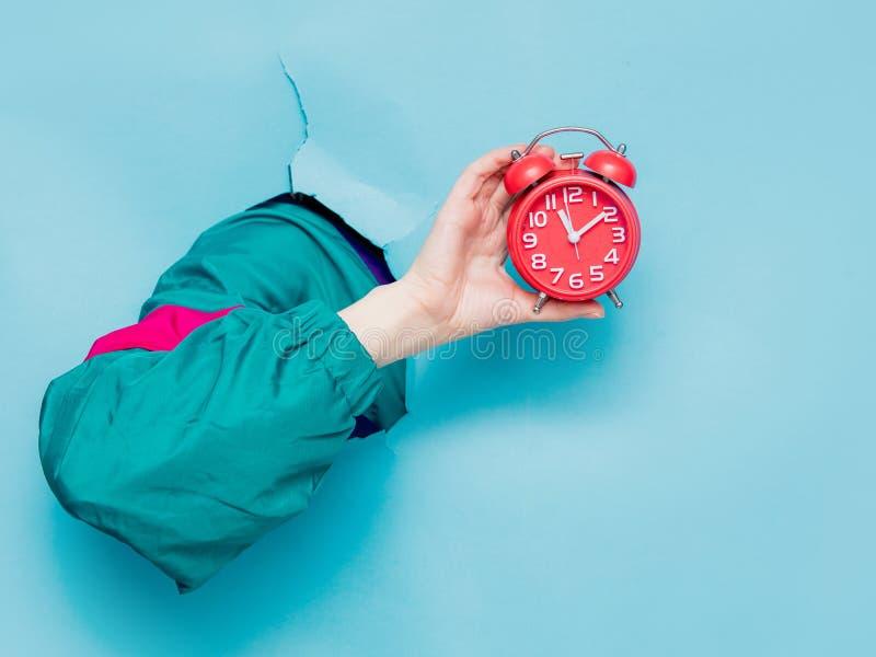 Mano femenina en despertador de la tenencia de la chaqueta del estilo 90s imágenes de archivo libres de regalías