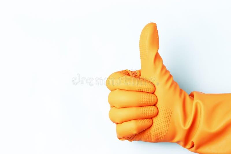Mano femenina en guantes de goma anaranjados con aumentado para arriba su pulgar en un fondo blanco fotografía de archivo