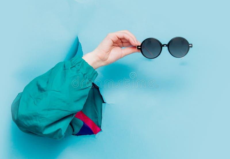 Mano femenina en la chaqueta del estilo 90s que lleva a cabo suglasses imagenes de archivo
