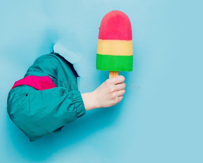 Mano femenina en la chaqueta del estilo 90s que sostiene el helado fotos de archivo libres de regalías