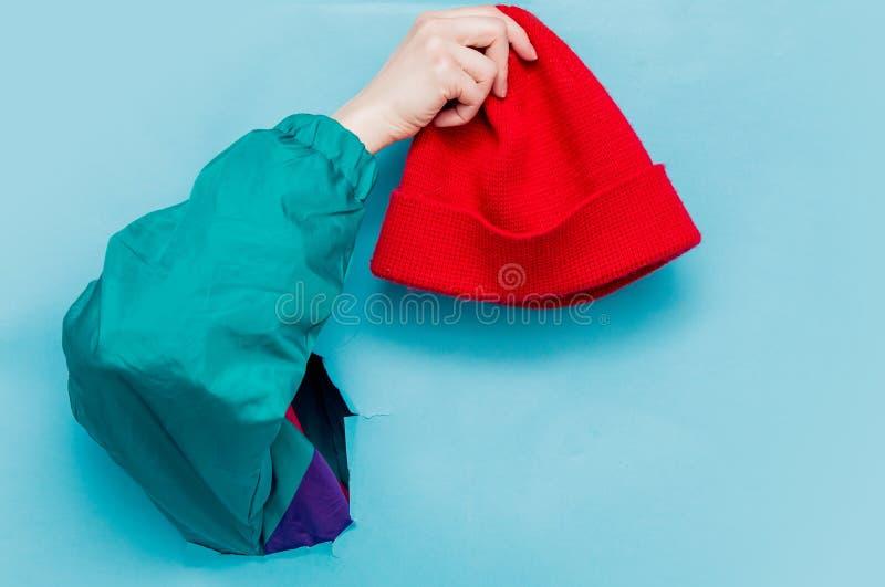 Mano femenina en la chaqueta del estilo 90s que sostiene el sombrero rojo imagen de archivo libre de regalías