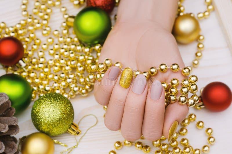 Mano femenina hermosa con diseño beige del clavo Manicura de la Navidad fotos de archivo