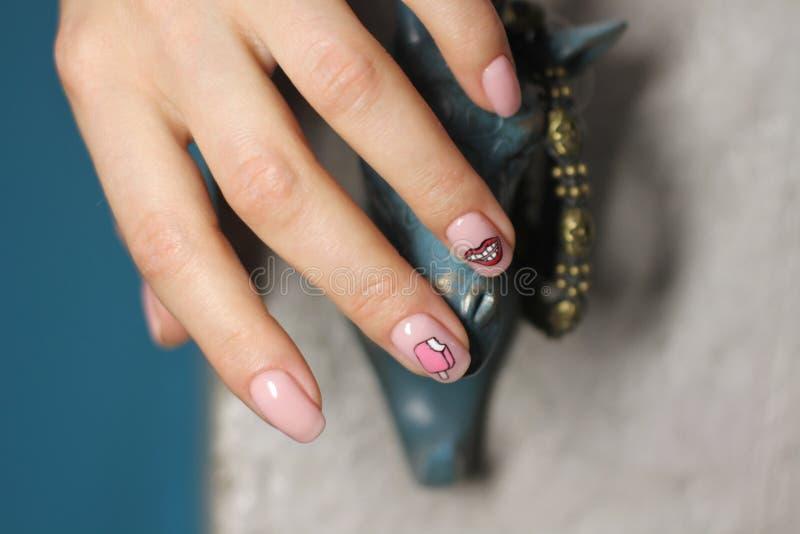 Mano femenina hermosa con la manicura Esmalte de uñas rosa claro con diseño creativo Etiquetas engomadas de los labios y del hela imágenes de archivo libres de regalías