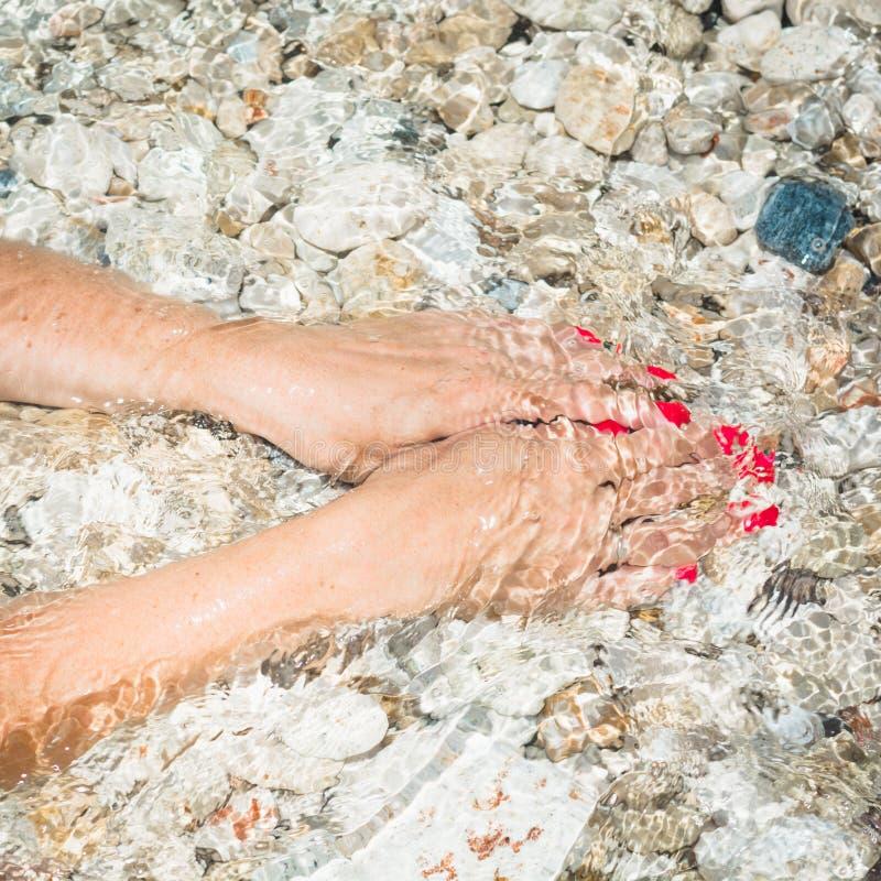Mano femenina hermosa en la agua de mar limpia Concepto del balneario de Eco fotos de archivo libres de regalías
