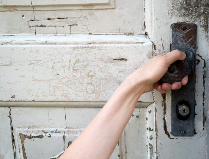 Mano femenina que alcanza para arriba para dar vuelta a un botón de puerta en una puerta de madera vieja imágenes de archivo libres de regalías
