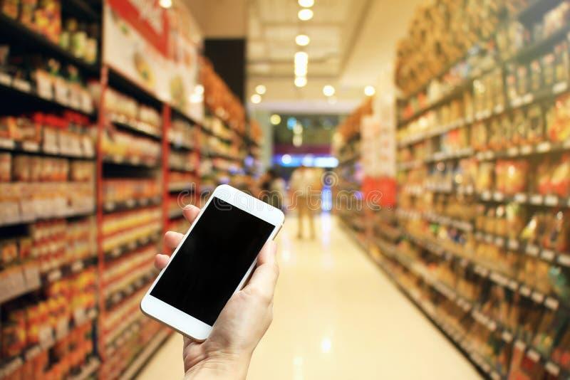 Mano femenina que celebra smartphone en el supermercado y que comprueba la lista de compras, compras en línea en concepto del uso foto de archivo libre de regalías