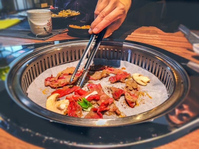 Mano femenina que cocina la carne de vaca coreana del griller del bulgogi en una parrilla del Bbq en la tabla del restaurante fotos de archivo libres de regalías