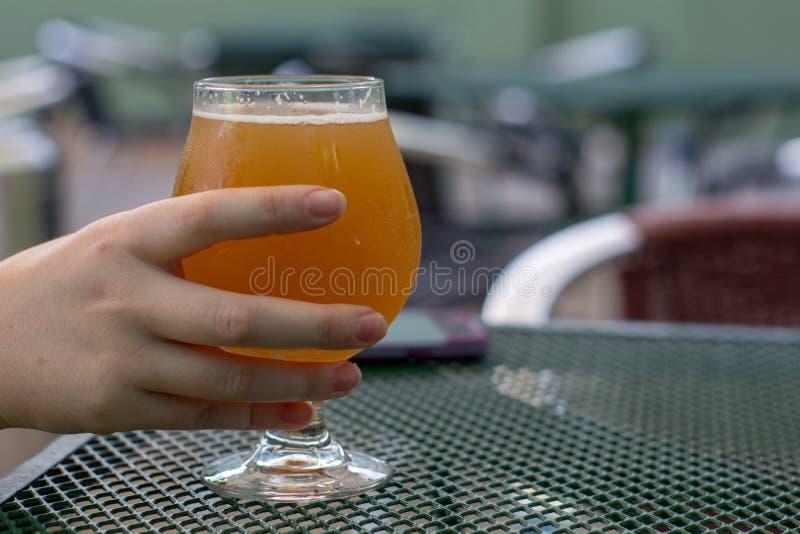 Mano femenina que coge su cerveza de una tabla fotos de archivo