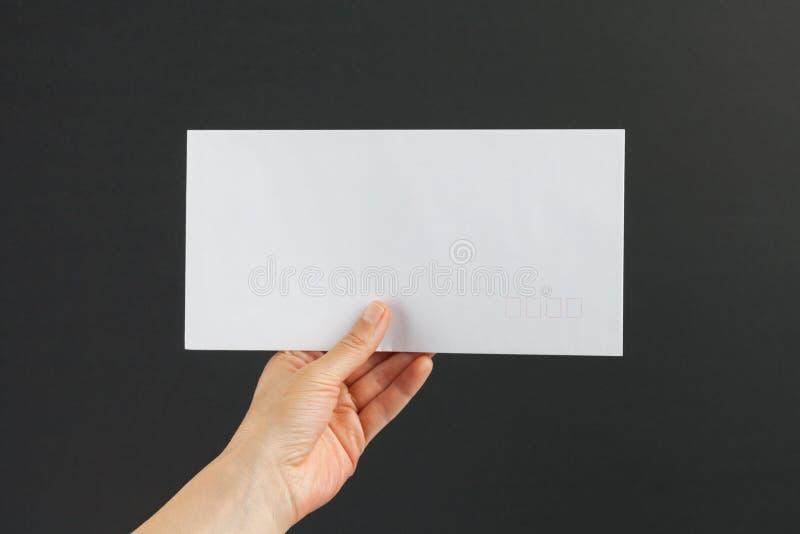 Mano femenina que entrega un sobre blanco en fondo negro fotos de archivo