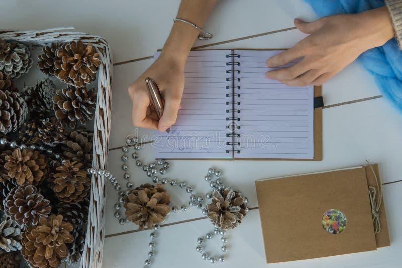 Mano femenina que escribe la letra de Papá Noel en el fondo de madera blanco con las decoraciones de la Navidad, los conos de abe imagen de archivo