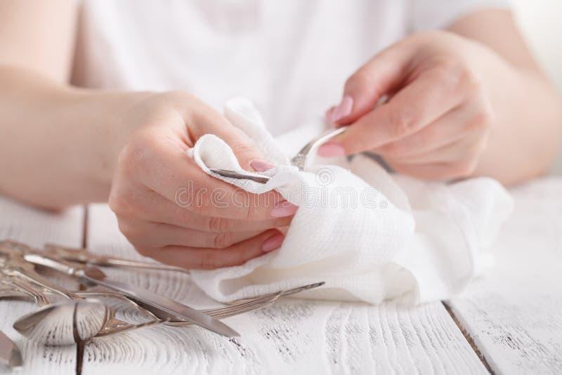 Mano femenina que limpia los cubiertos manchados con un producto de limpieza a foto de archivo