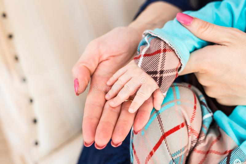Mano femenina que lleva a cabo la mano recién nacida del ` s del bebé imagenes de archivo