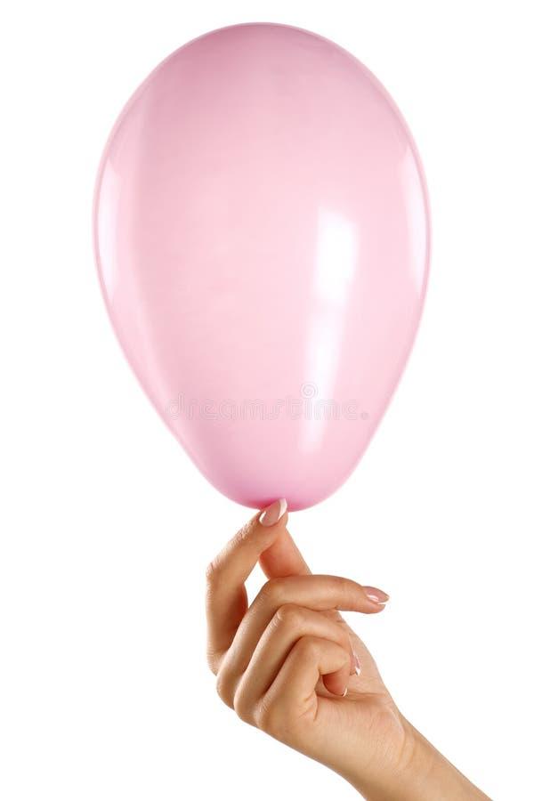 Mano femenina que lleva a cabo un pequeño baloon rosado fotos de archivo