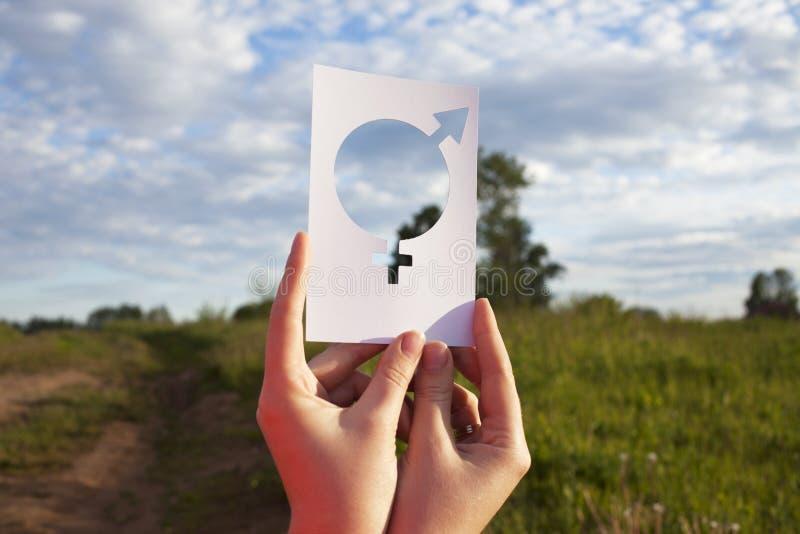 Mano femenina que lleva a cabo un símbolo de la igualdad de género contra la perspectiva del cielo azul con las nubes fotografía de archivo