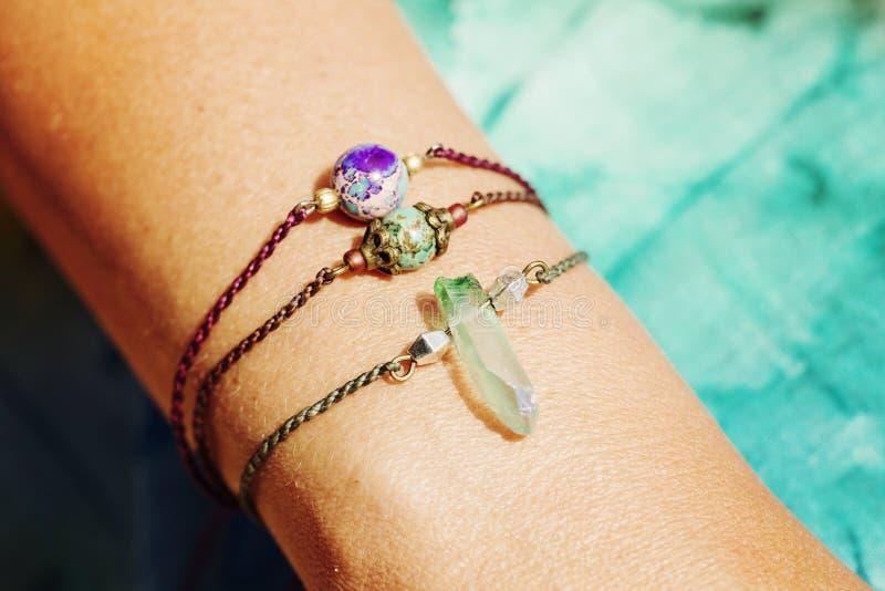 Mano femenina que lleva las pulseras de piedra naturales de la gota foto de archivo libre de regalías