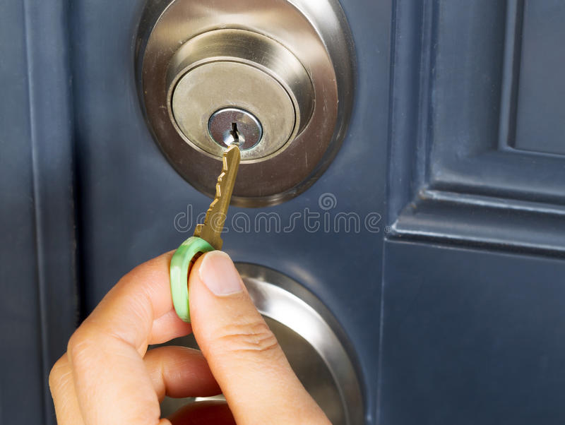 Mano femenina que pone llave de la casa en la cerradura de puerta foto de archivo