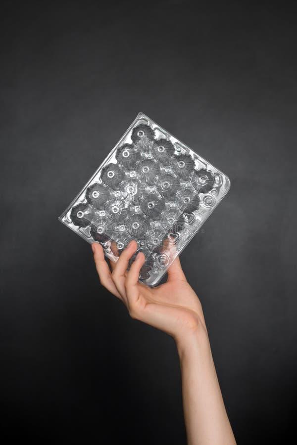 Mano femenina que sostiene el envase de plástico vacío para los huevos aislados en fondo negro Basura reciclable Reciclando, reut foto de archivo libre de regalías