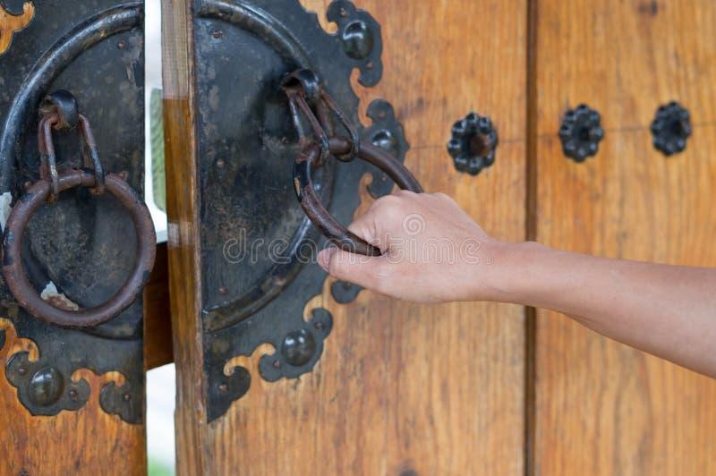 Mano femenina que sostiene el golpeador de puerta antiguo foto de archivo