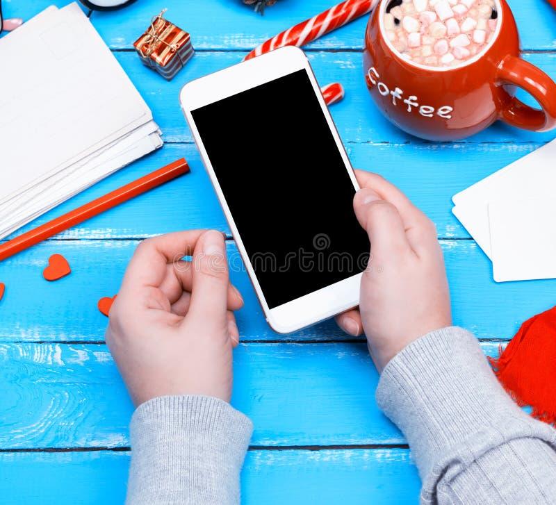 Mano femenina que sostiene el teléfono elegante blanco con la pantalla negra en blanco imágenes de archivo libres de regalías