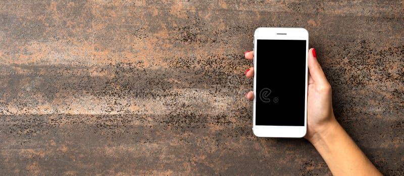 Mano femenina que sostiene el teléfono móvil blanco con la pantalla vacía negra fotografía de archivo libre de regalías