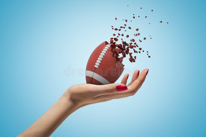 Mano femenina que sostiene la bola del fútbol americano que rompe en pedazos en fondo azul fotos de archivo libres de regalías