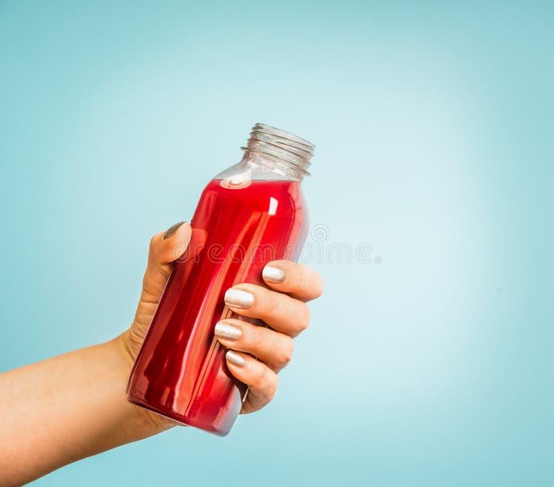 Mano femenina que sostiene la botella con la bebida roja del verano: smoothie o jugo en el azul fotos de archivo