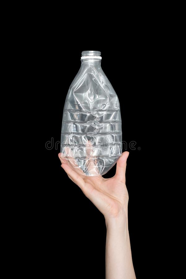 Mano femenina que sostiene la botella plástica machacada vacía aislada en fondo negro Basura reciclable Reciclando, reutilización fotos de archivo