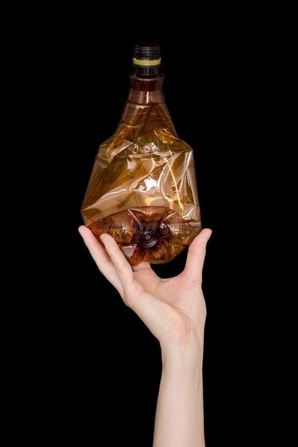 Mano femenina que sostiene la botella plástica machacada vacía aislada en fondo negro Basura reciclable Reciclando, reutilización fotografía de archivo