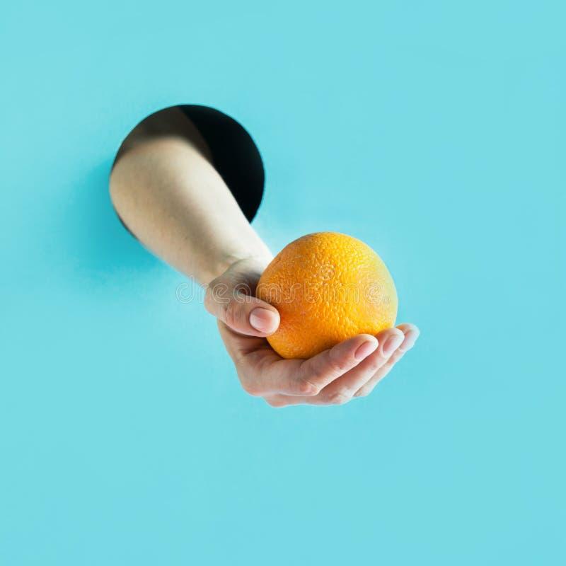 Mano femenina que sostiene la naranja madura en agujero del papel fotografía de archivo