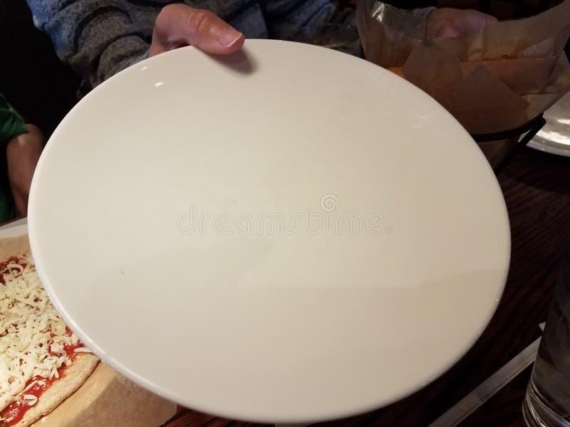 Mano femenina que sostiene la placa y la pizza blancas con queso imagen de archivo libre de regalías