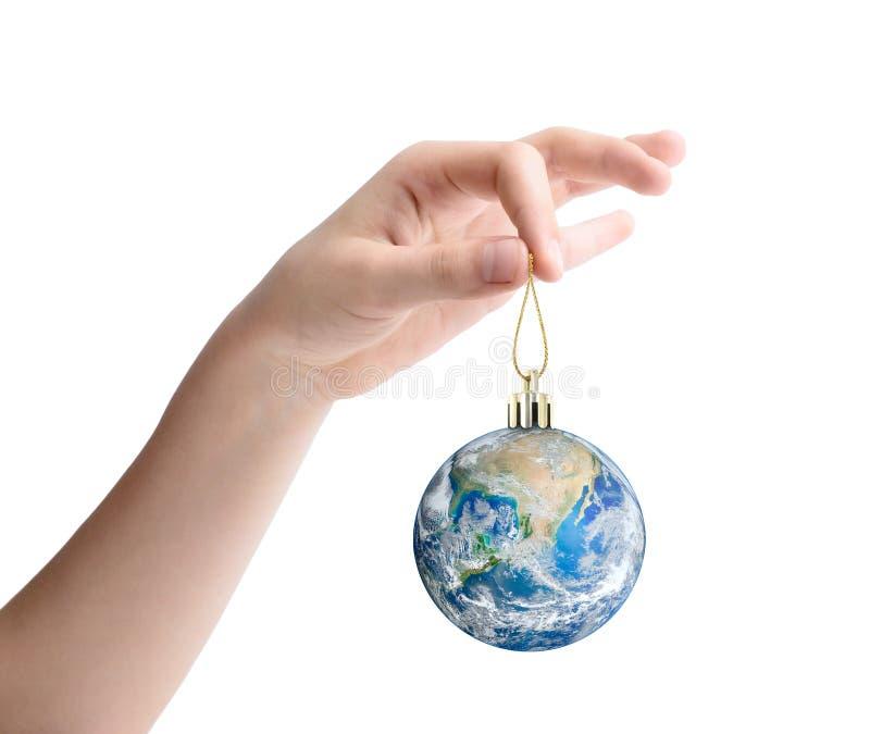 Mano femenina que sostiene la tierra del planeta como juguete de la Navidad Elementos de esta imagen equipados por la NASA foto de archivo