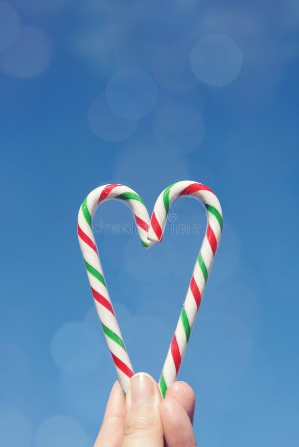 Mano femenina que sostiene los bastones del caramelo en la forma de un corazón fotografía de archivo libre de regalías