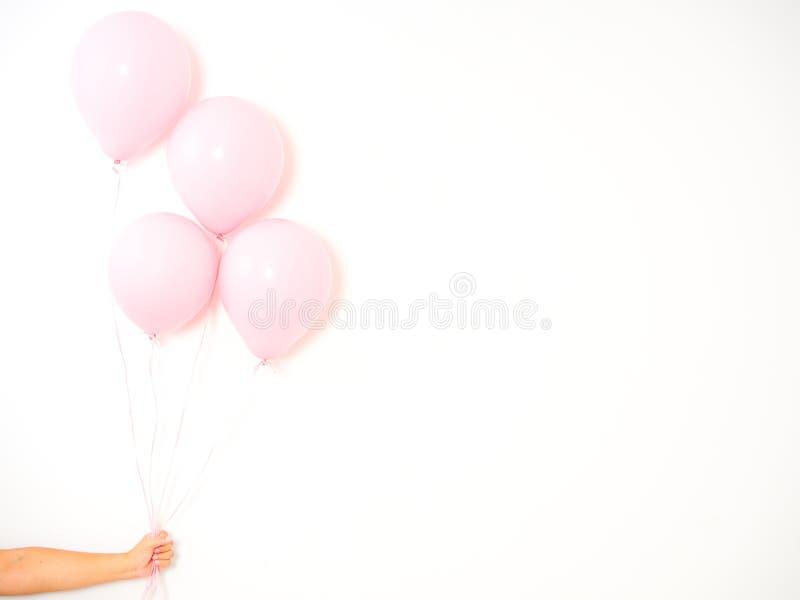 Mano femenina que sostiene los globos rosados fotografía de archivo libre de regalías
