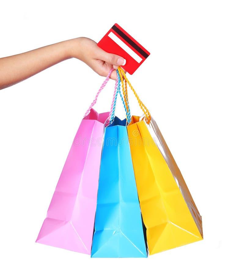 Mano femenina que sostiene los panieres y la tarjeta de crédito coloridos foto de archivo libre de regalías