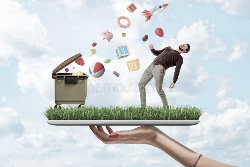 Mano femenina que sostiene un modelo de la hierba con un hombre en ropa casual y el bote de basura con los objetos al azar que ca fotos de archivo