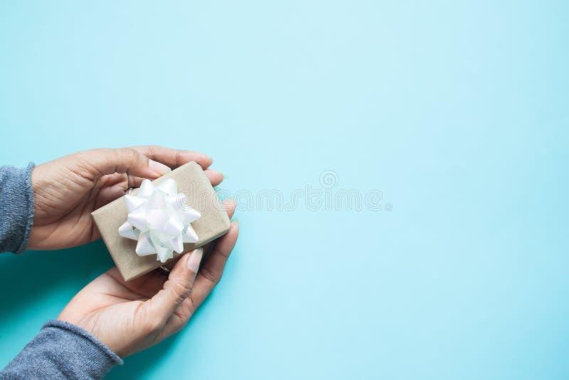 Mano femenina que sostiene un pequeño regalo envuelto con la cinta blanca en el bl fotos de archivo