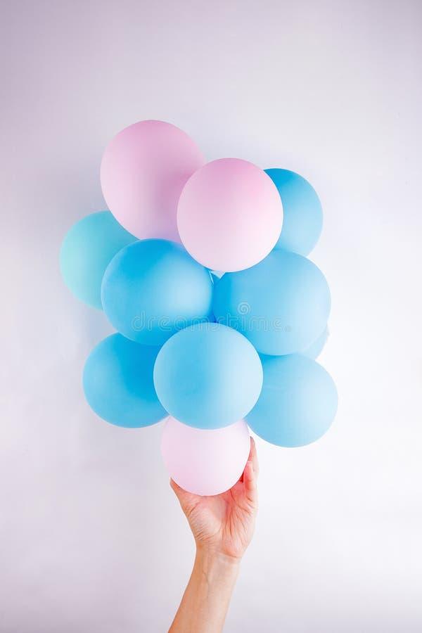 Mano femenina que sostiene un pequeño rosa determinado y un lika azul de los baloons una nube en el fondo blanco fotografía de archivo