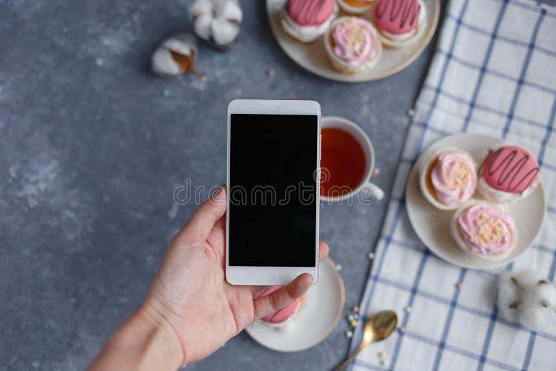 Mano femenina que sostiene un smartphone en el fondo de la tabla con la torta, una taza de té Desayuno imagen de archivo libre de regalías