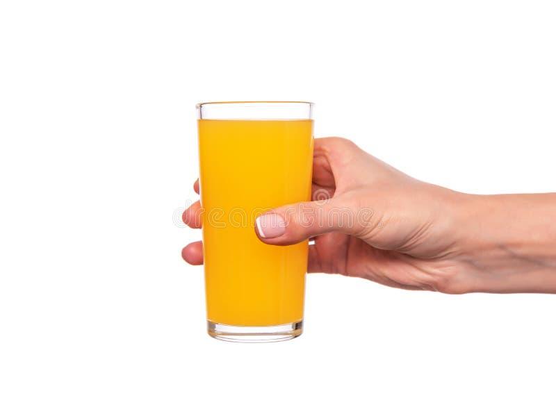 Mano femenina que sostiene un vidrio con el jugo anaranjado o de la fruta cítrica en el fondo blanco foto de archivo